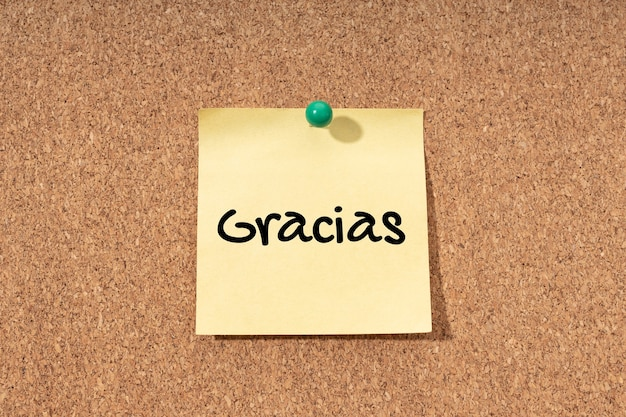 Thank you in spanish written on yellow post it on corck board background