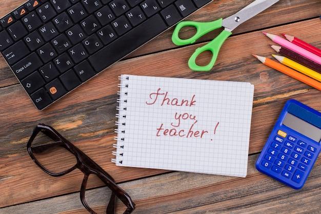 Спасибо, учитель! школьные принадлежности на коричневом деревянном столе.