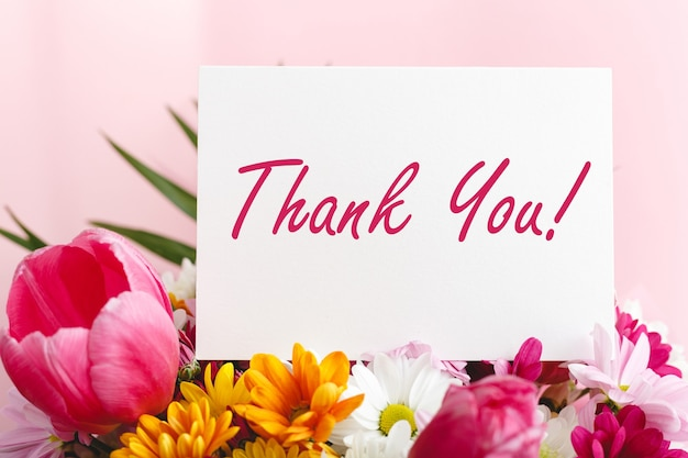 Thank you text card in beautiful flowers bouquet on pink background white blank copy space
