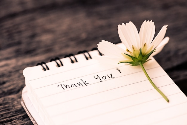 Thank you text on a white page note book with romantic white flower