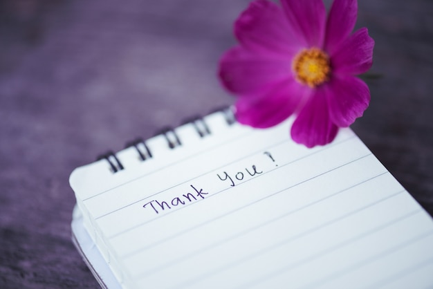 Thank you text on a white page note book with white flower