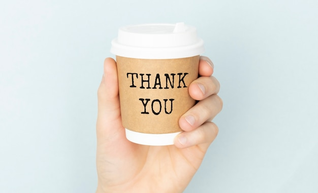 Thank you or thank you concept with a cup of coffee in hands on a light background.