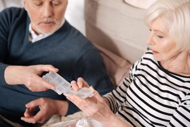 감사합니다. 그의 아픈 아내가 약을 복용하는 동안 투명 알약 케이스를 들고 노인의 상위 뷰.