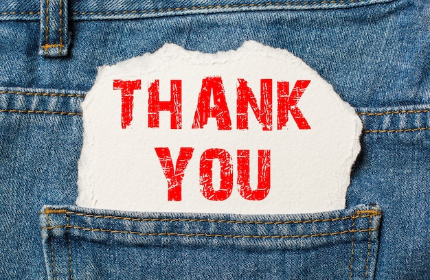Thank you on white paper in the pocket of blue denim jeans