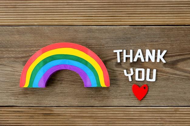 Спасибо слово, концепция благодарности с красным сердцем и радугой.