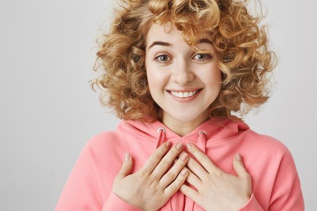 Благодарная милая девушка рада или польщена, оптимистично улыбается