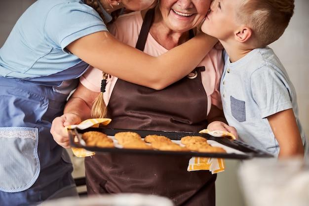 아이들의 사랑을 받는 신선한 쿠키를 들고 감사하는 할머니