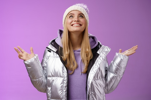 Thankful happy cute attractive blond young 25s woman in winter hat silver trendy jacket raise hands look up grateful god dream come true smiling delighted fulfilled wish, purple background.