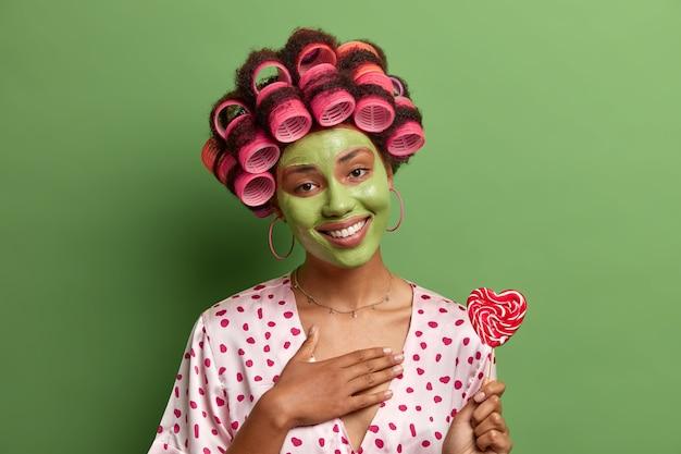 Grata e compiaciuta giovane donna con un sorriso a trentadue denti, preme la mano sul petto, indossa bigodini e vestaglia di seta, applica una maschera idratante di avocado, tiene caramelle a forma di cuore, isolato su verde
