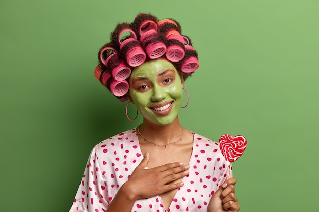 歯を見せる笑顔で感謝の気持ちを表す若い女性、手を胸に押し付け、ヘアカーラーとシルクのローブを身に着け、保湿アボカドマスクを適用し、ハート型のキャンディーを保持し、緑で隔離