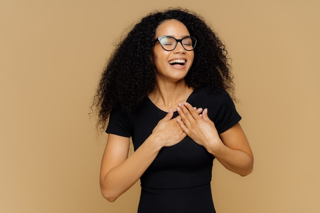 Thankful positive woman smiles happily, makes gratitude gesture, keeps hands on chest