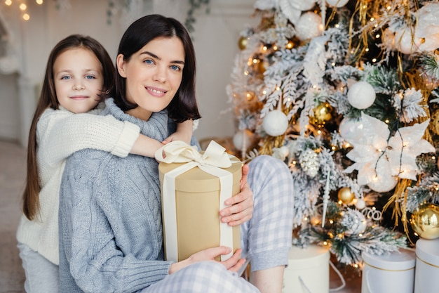 Thankful small female child embraces her mother who gave present, spend wonderful unforgettable time together, celebrate christmas. brunette woman and daughter look for present gifts under fir tree