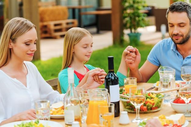 食事をありがとう。屋外のテーブルに座って手をつないで夕食前に祈る家族