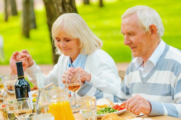 食事をありがとう。屋外のテーブルに座って手をつないで家族の夕食の前に祈る年配のカップル