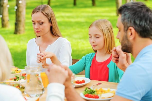 食事を神に感謝します。屋外のテーブルに座って手をつないで夕食前に祈る家族