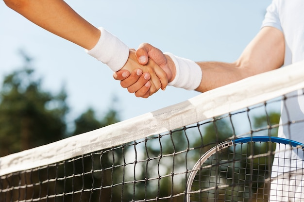 Thanking for good game. close-up of man and woman in wristband shaking hands upon the tennis net