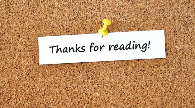 読んでくれてありがとう。一枚の紙やメモ、コルクボードの背景に書かれたテキスト。
