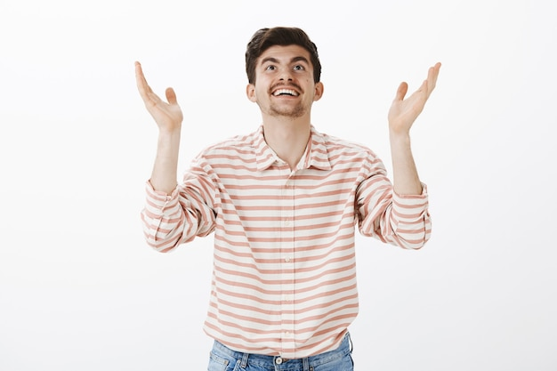Thanks god it is friday. portrait of grateful successful male teacher in striped shirt, raising hands and looking up with broad relieved smile, thanking heavens for vacation, standing over gray wall