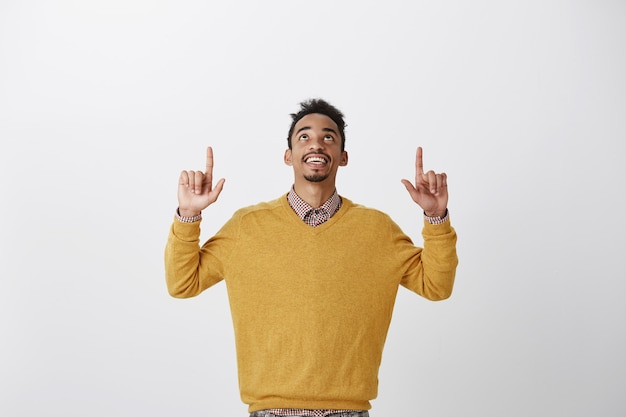 Thanks god it is friday. portrait of pleased interested young african-american student in stylish yellow sweater raising hands, looking and pointing up, enjoying nice view of sky