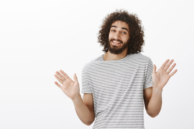 Thanks but i pass. carefree good-looking eastern guy with curly hair, raising palms and waving them near chest in rejection gesture, smiling awkwardly and denying involvement