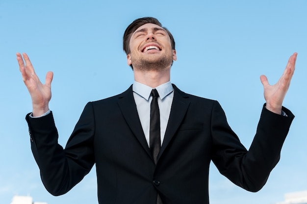 하나님께 감사합니다! 푸른 하늘을 배경으로 서서 손을 들고 웃고 있는 정장 차림의 잘생긴 청년