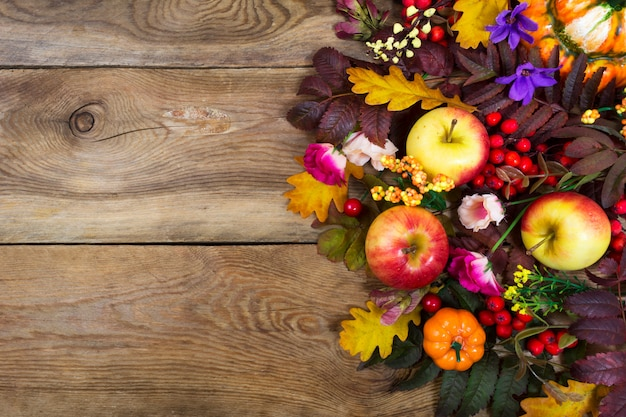 Thanksgiving arrangement with apples, fall leaves, pink and purple flowers,