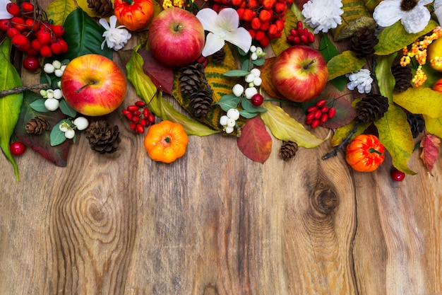 Thanksgiving arrangement with pumpkins, apples, leaves, rowan berries and white flowers