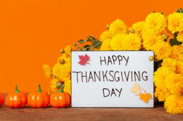 Thanksgiving autumn composition with yellow flower and pumpkins on orange background. lightbox with the phrase happy thanksgiving day. autumn holidays, fall concept.