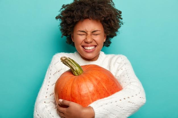 Ringraziamento e concetto di tempo autunnale. gioiosa donna dalla pelle scura abbraccia il raccolto autunnale, grande zucca arancione