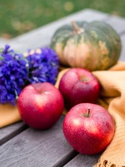 感謝祭の背景:木製の背景にリンゴ、カボチャ、青いヤグルマギクの花。テキスト用のスペースをコピーします。