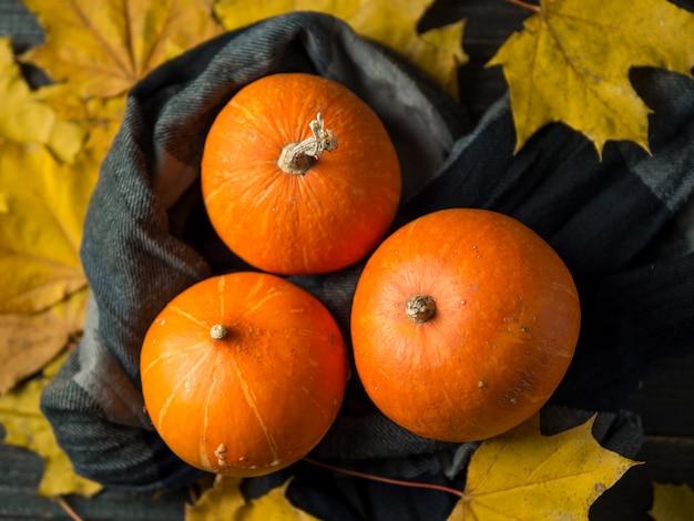 Thanksgiving background, orange pumpkins and autumn leaves on dark wooden background