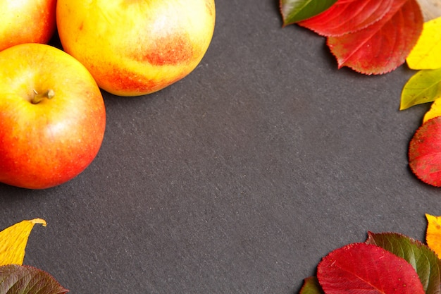 Thanksgiving background with apples and fall leaves.