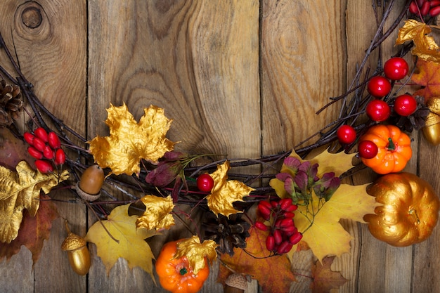 Thanksgiving background with golden pumpkin, acorn and maple leaves wreath,
