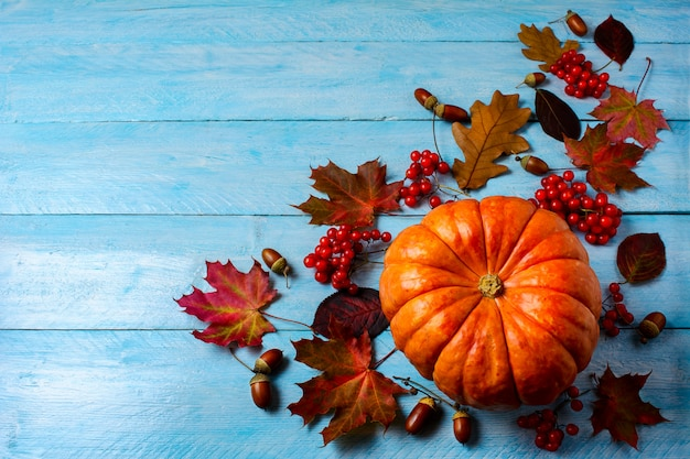 Thanksgiving background with ripe pumpkin on blue wooden table