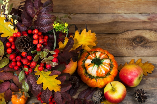 Thanksgiving background with rowan and oak leaves on wooden table,