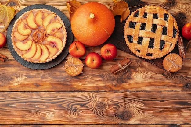 感謝祭のベリーとリンゴの木製の表面、上面図、コピースペースのさまざまなパイ