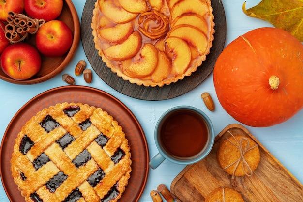 Ягоды благодарения и яблоки различные пироги на деревянной поверхности, вид сверху, копия пространства