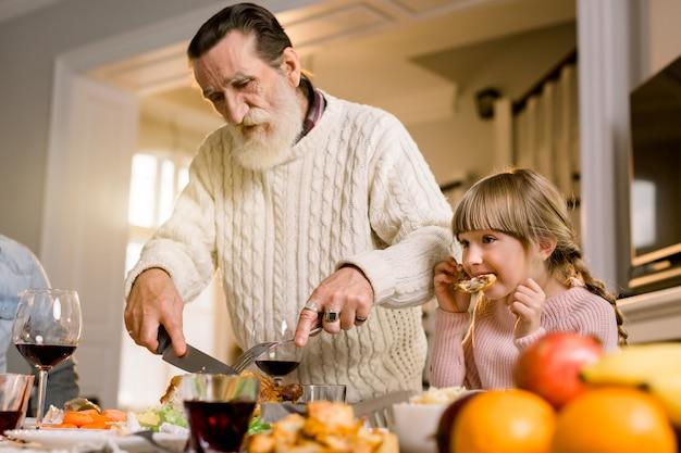 Концепция семейного ужина традиции торжества благодарения. семья с праздничным ужином и нарезкой индейки. старый красивый дедушка и его внучка