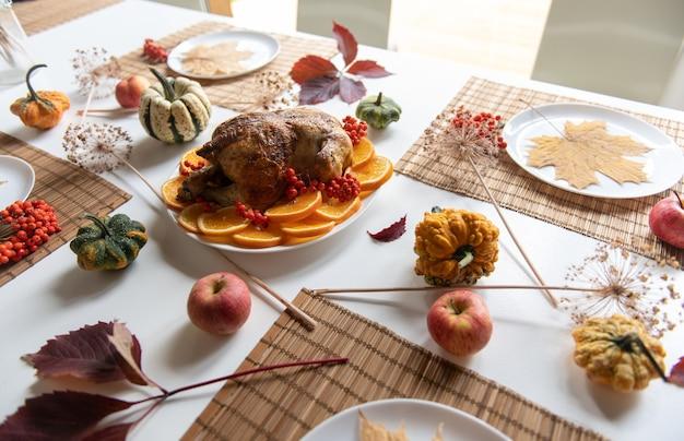 感謝祭のお祝いの伝統的な夕食の設定食品の概念。装飾されたテーブルの上のローストターキーの上面図。