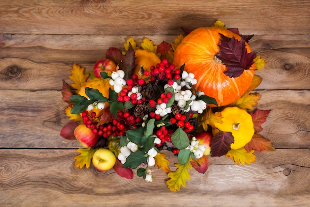 Thanksgiving centerpiece with snowberry and pumpkins on wooden background