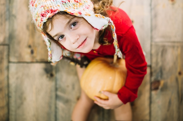 Thanksgiving concept with girl holding pumpkin