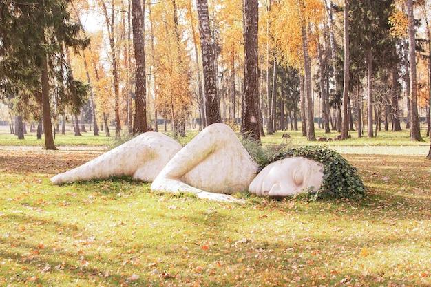 День благодарения. осенний праздник в парке фиура женщина из камня. листопад на траву. концепция осеннего времени