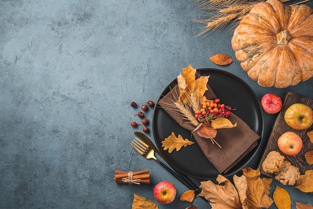 День благодарения фон с черной тарелкой, салфеткой, столовыми приборами, тыквой и осенними листьями