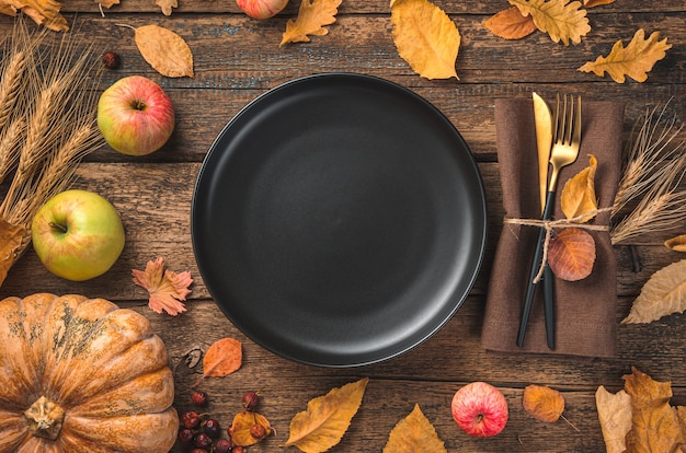 Thanksgiving day background with a black plate cutlery pumpkin apples and autumn leaves