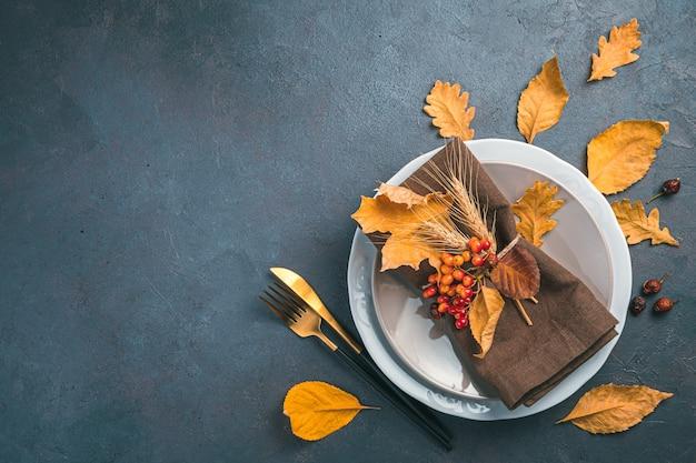 濃いグレーブルーの背景にカトラリーナプキンと乾燥した葉を持つ感謝祭の日の背景