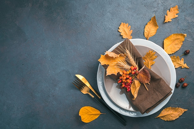 Thanksgiving day background with cutlery napkin and dry leaves on a dark grayblue background