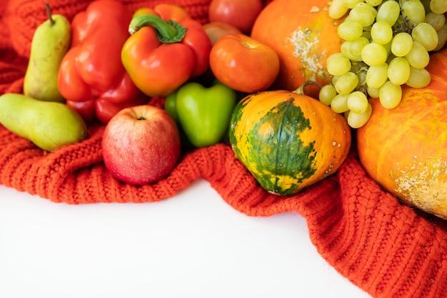 感謝祭。大きな秋の収穫-白い背景と赤い布に梨、リンゴ、カボチャ、コショウ、トマト。感謝祭のお祝いのコンセプト。