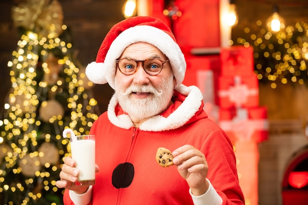 Thanksgiving day and christmas happy santa claus eating a cookie and drinking glass of milk at home ...