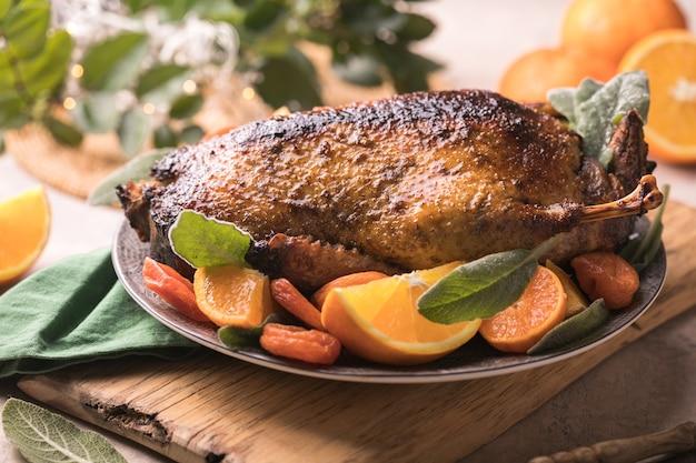Ужин в день благодарения с жареной уткой, украшенной апельсином и зеленью.