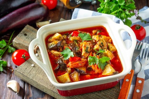 感謝祭の日の食べ物の概念暗い素朴な背景に野菜と自家製の七面鳥の煮込み